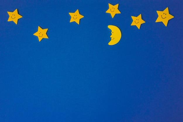 Halbmond und gelbe sterne gegen den blauen nächtlichen himmel. bewerbungsunterlagen. Premium Fotos