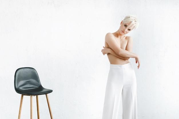 Halbnacktes modell in der weißen hose steht vor einer weißen wand im studio Kostenlose Fotos