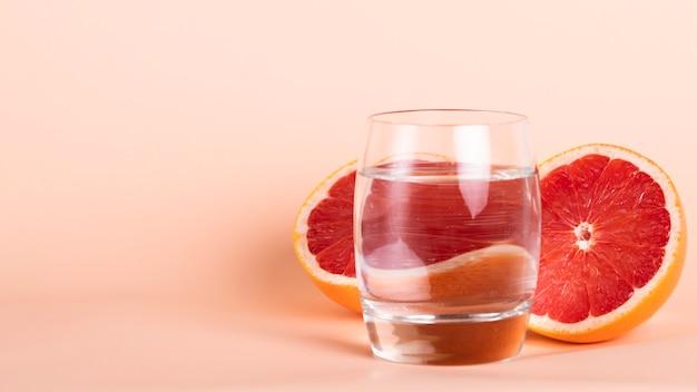Halbrote orange und glas auf wasseranordnung Kostenlose Fotos