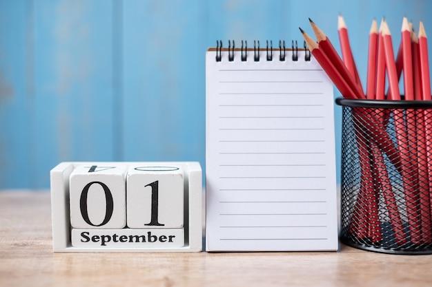 Hallo september kalender, willkommen zurück in der schule mit notizbuch und stiften. platz für text kopieren Premium Fotos