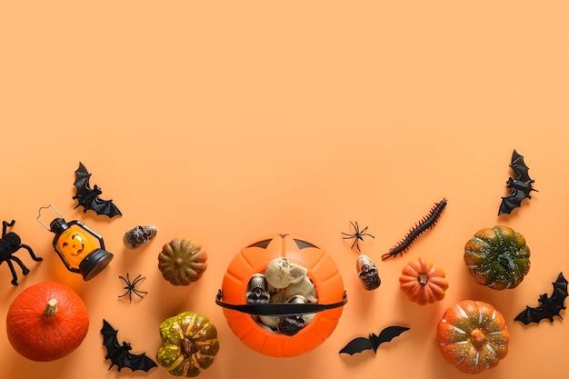 Halloween-banner der lustigen partydekorationen, der süßigkeitenschale, der kürbisse, der süßigkeiten, der fledermaus, der schädel, der gespenstischen spinne auf orangefarbenem hintergrund. Premium Fotos