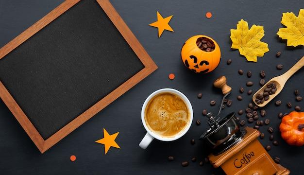 Halloween-dekoration mit heißem kaffee und bohnen auf dunklem hintergrund. flach liegen. kopieren sie platz für text. Premium Fotos