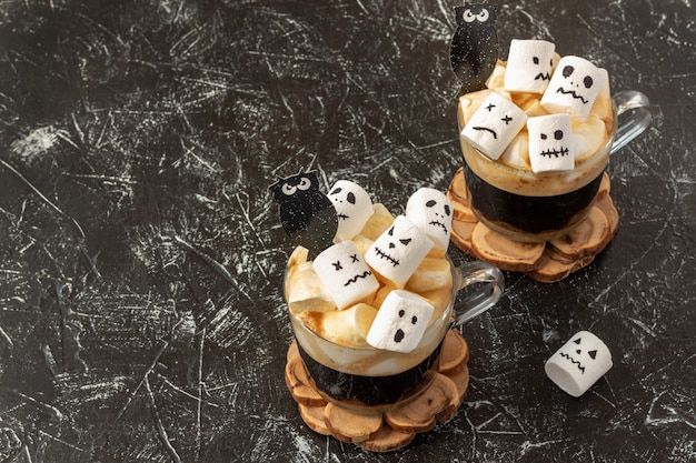 Halloween-drink - gruselige gesichter (monster) von marshmallows in einer tasse kaffee Premium Fotos