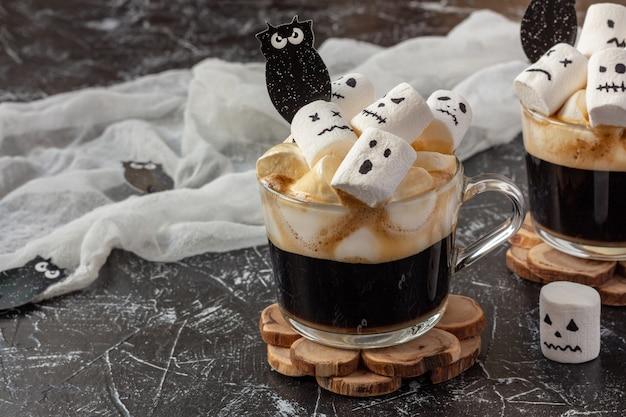 Halloween-getränk - zwei tassen kaffee mit marshmallow (gruselige gesichter, monster) auf dunklem tisch Premium Fotos