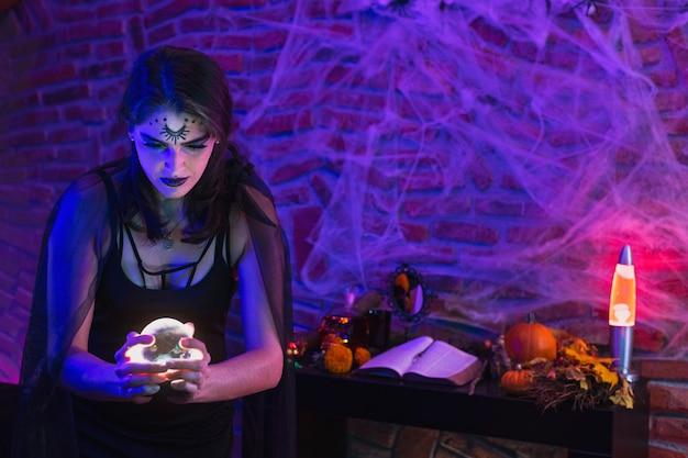 Halloween-hexe, junge frau, verkleidet als wicca, die einen magischen ball über spinnennetz hält Premium Fotos