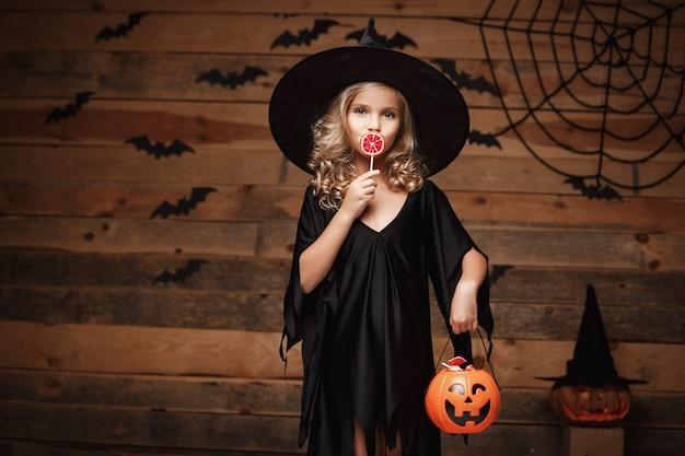 Halloween-hexe-konzept - kleine hexe kind mit halloween süß und süßigkeiten mit fröhlichen lächeln. über fledermaus und spinnennetz hintergrund. Premium Fotos