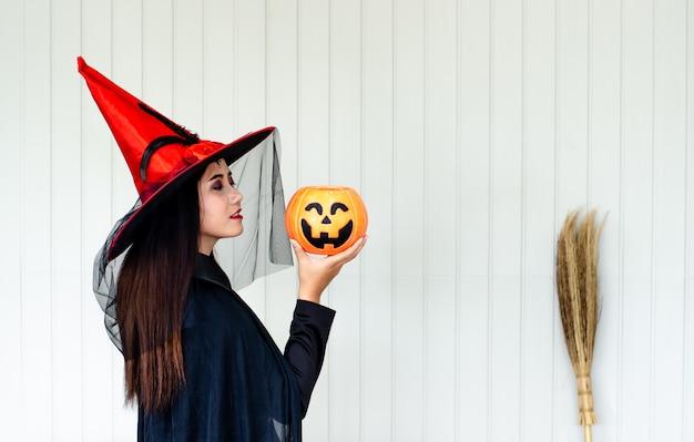 Halloween-hexe mit einem magischen kürbis, schöne junge frau im hexenhut und -kostüm Premium Fotos