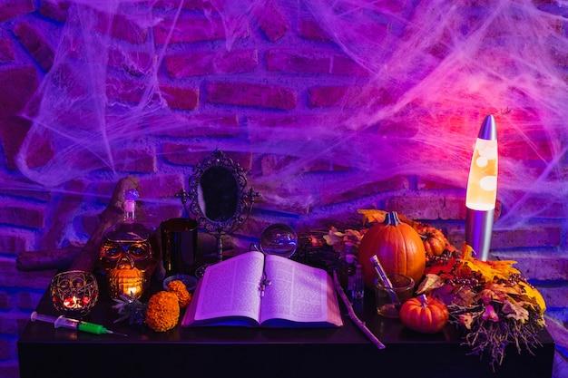 Halloween hexentisch, altar mit magischen gegenständen, antikes buch für einen zauber, brennende kerzen und kürbis Premium Fotos