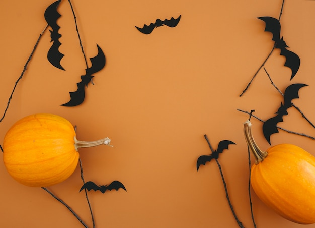 Halloween hintergrund mit kürbissen, fledermäusen, dekorationen auf orange hintergrund. halloween-partyeinladungskartenmodell mit kopienraum. Premium Fotos