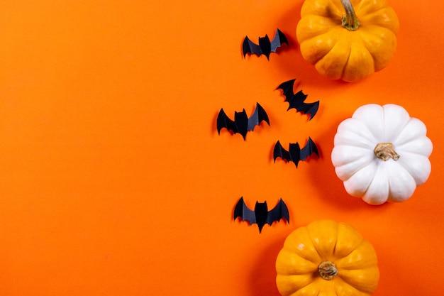Halloween-konzept. menge von schwarzen papierschlägern und von frischem kürbis auf orange papierhintergrund. Premium Fotos