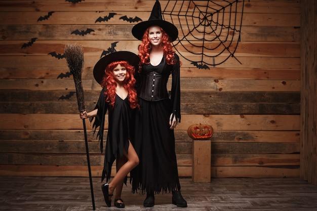 Halloween-konzept - schöne kaukasisch mutter und ihre tochter mit langen roten haaren in hexenkostüme feiern halloween posiert Premium Fotos