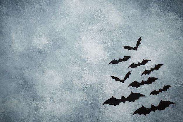 Halloween-konzept. schwarze papierfledermäuse auf grau Premium Fotos
