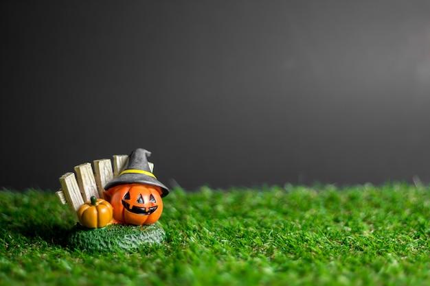 Halloween-kürbis, der einen hut auf dem gras trägt. Premium Fotos