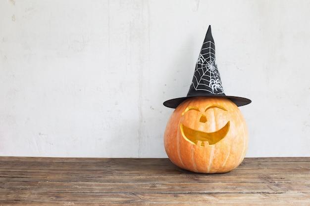 Halloween-kürbis im schwarzen hut auf holztisch Premium Fotos