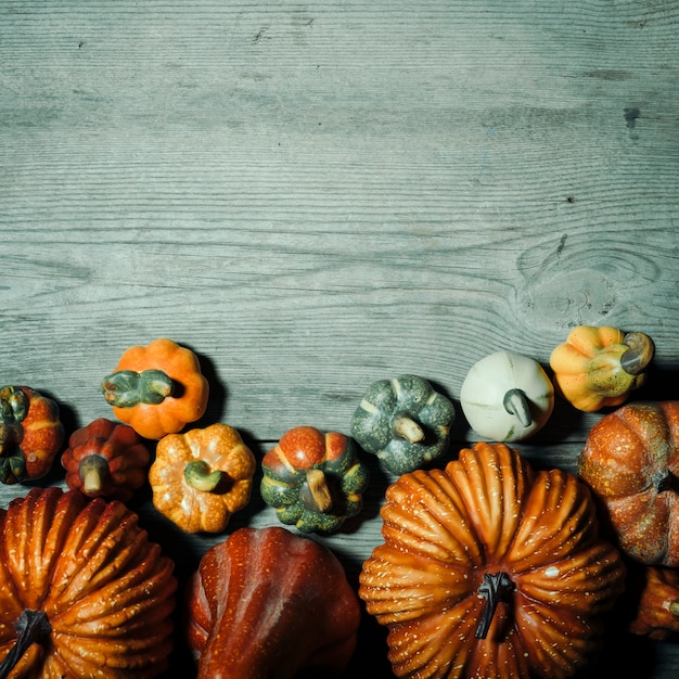 Halloween-kürbise mit kopienraum über hölzernem hintergrund Kostenlose Fotos