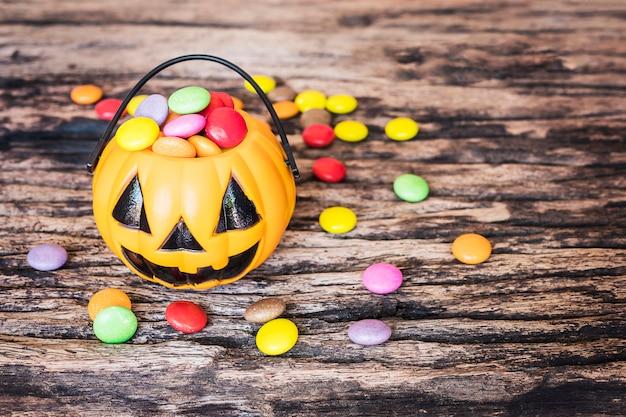 Halloween-kürbisgesichtseimer mit bunter süßigkeit nach innen auf alter hölzerner beschaffenheit Kostenlose Fotos