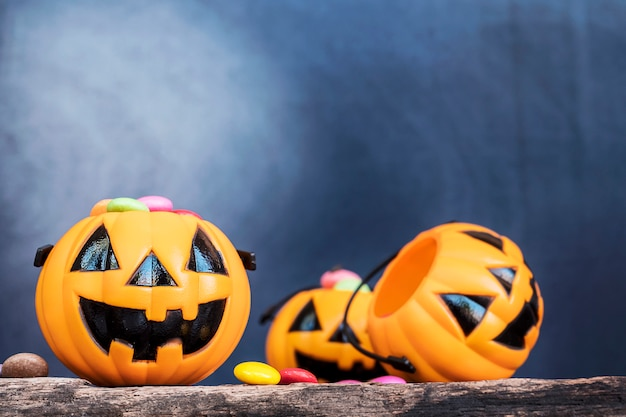 Halloween-kürbisgesichtseimer mit bunter süßigkeit nach innen auf alter hölzerner planke Kostenlose Fotos