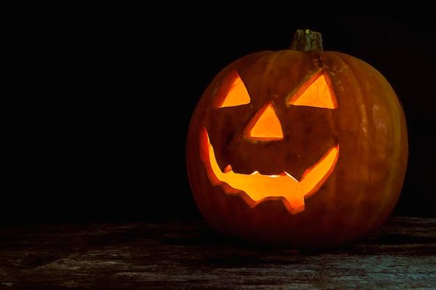 Halloween-kürbiskopfsteckfassungslaterne auf hölzernem hintergrund Kostenlose Fotos