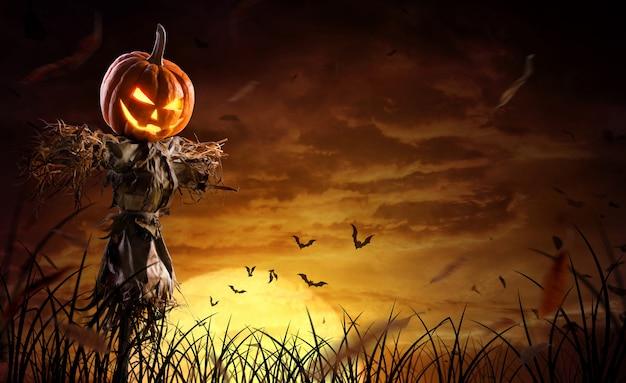 Halloween-kürbisvogelscheuche auf einem breiten feld mit dem mond in einer furchtsamen nacht Premium Fotos