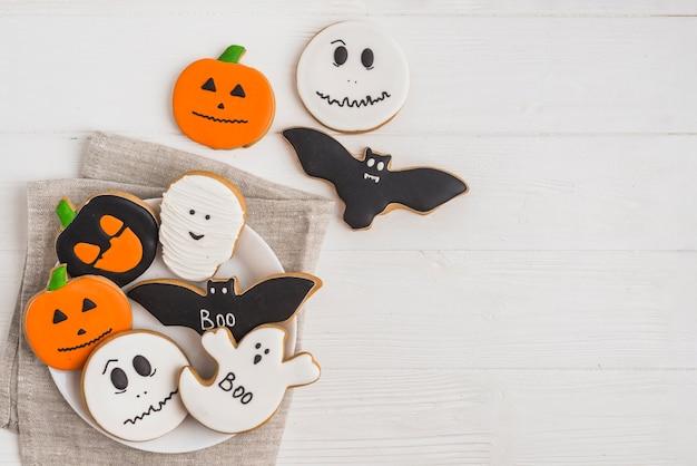 Halloween-lebkuchen auf dem teller gelegt auf stoff Kostenlose Fotos
