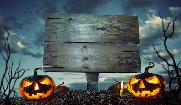 Halloween-nacht-konzept. leeres holzschild mit copyspace und furchtsamen kürbisen Premium Fotos