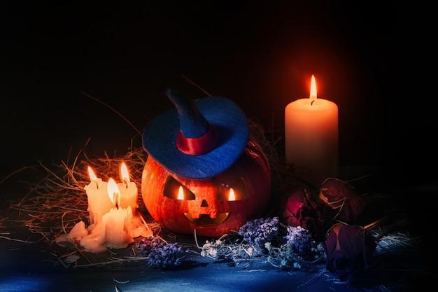 Halloween orange kürbis mit geschnitztem gesicht. furchtsamer kürbis mit kerzen und einem purpurroten hexenhut Premium Fotos