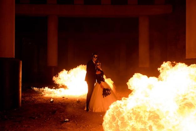 Halloween-paare, die mit flammenwerfer stehen. großes feuer Premium Fotos