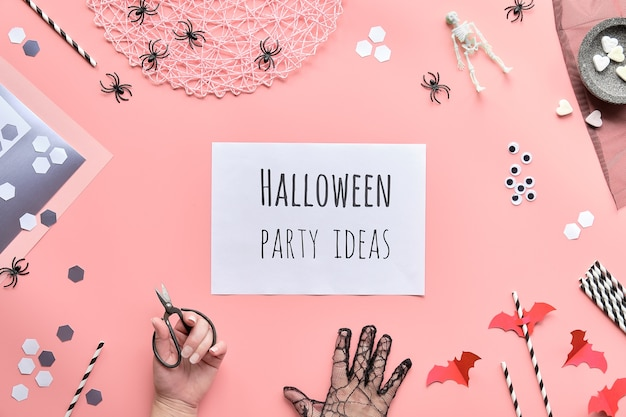 Halloween party ideen text auf weißer seite in der hand gehalten. flach mit schere und dekoration auf rosa papier liegen Premium Fotos