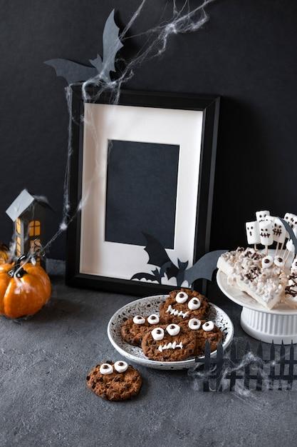 Halloween schokoriegel: lustige monster aus keksen mit schokolade und geister marshmelow nahaufnahme auf dem tisch Premium Fotos