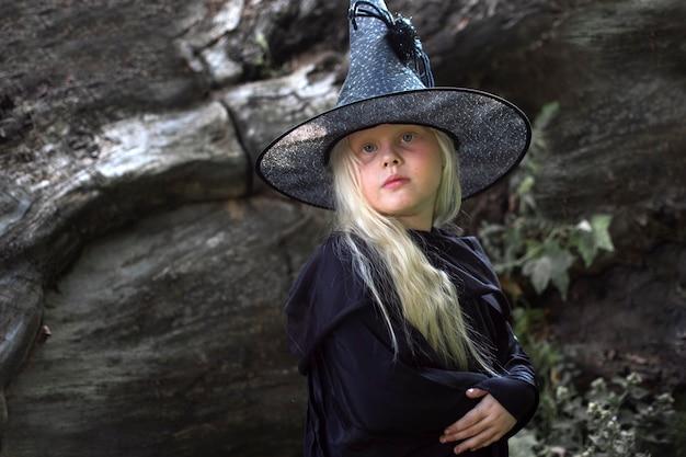 Halloween und hexen. kind im bild einer hexe mit weißen haaren in einer dunklen höhle, feiertag Premium Fotos