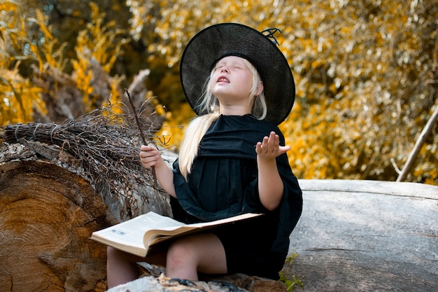 Halloween und hexen. kind in einem hexenkostüm. das kind sitzt mit einem buch und einem zauberstab auf einem baum. herbst, wald Premium Fotos