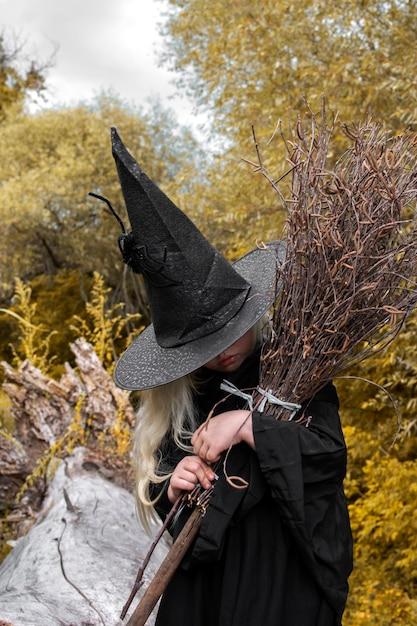 Halloween und hexen. mädchen in einem schwarzen hut mit einem besen in seinen händen im herbstwald Premium Fotos