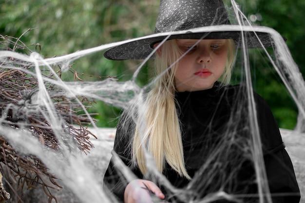 Halloween und kinder. mädchen in einem schwarzen hut mit spinnen und spinnweben, porträt Premium Fotos