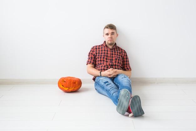 Halloween und maskerade-konzept - hübscher mann, der mit kürbis-jack-laterne aufwirft. Premium Fotos