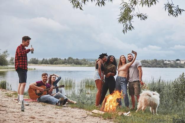 Halte den moment fest. eine gruppe von menschen hat ein picknick am strand. freunde haben spaß am wochenende. Premium Fotos