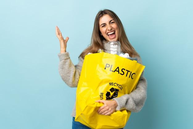Halten sie eine tasche voller plastikflaschen, um auf isoliertem blau unglücklich und frustriert mit etwas zu recyceln Premium Fotos