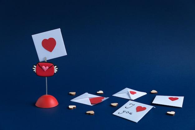 Halter mit valentinstag, umschläge mit nachrichten und hölzernen, kleinen herzen auf einem dunkelblauen papierhintergrund mit platz für text. Premium Fotos