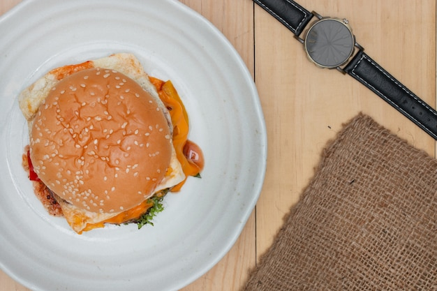 Hamburger mit armbanduhr auf hölzerner tabelle. Premium Fotos
