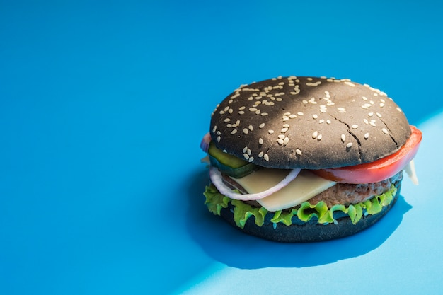 Hamburger mit schwarzem brötchen auf blauem hintergrund Kostenlose Fotos