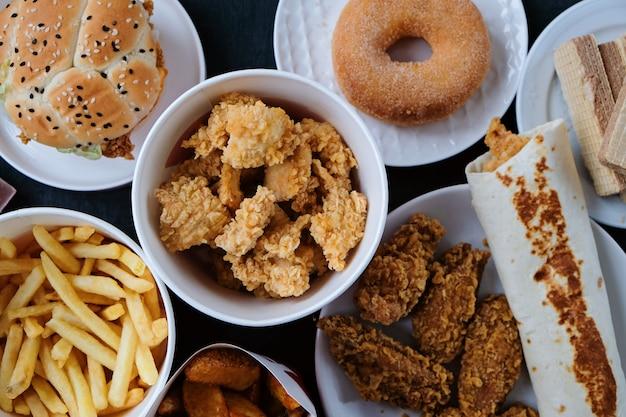 Hamburger, pommes frites, donut, nuggets und schokolade auf schwarz Premium Fotos