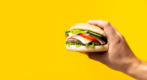Hamburger vor gelbem hintergrund gehalten Kostenlose Fotos