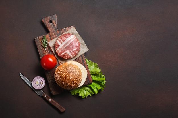 Hamburger zutaten rohes schnitzel, tomaten, salat, brötchen, käse, gurken und zwiebeln Premium Fotos