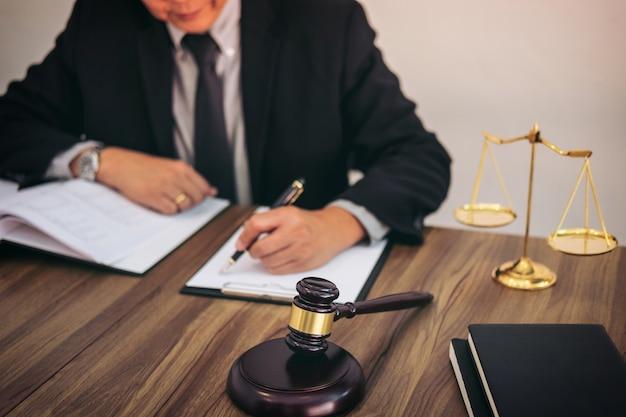 Hammer auf holztisch und rechtsanwalt oder richter, die mit vereinbarung im gerichtssaal arbeiten Premium Fotos
