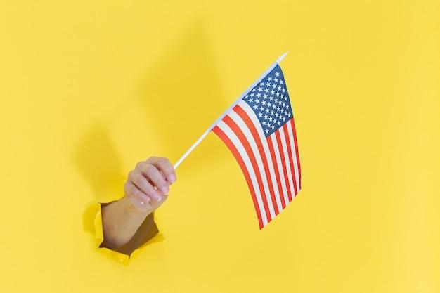 Hand aus einem loch in gelbem papier hält eine amerikanische flagge mit blauen sternen. amerika-unabhängigkeitstag-konzept. hand, die amerikanische flagge hält Premium Fotos