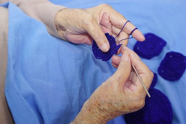 Hand der asiatischen älteren frau häkeln dunkelblaues garn Premium Fotos