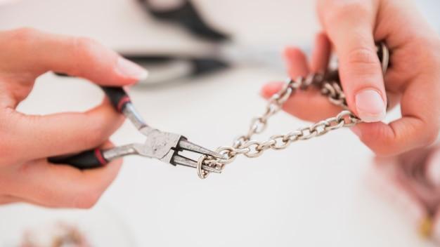 Hand der frau, die den metallischen haken mit zangen repariert Kostenlose Fotos