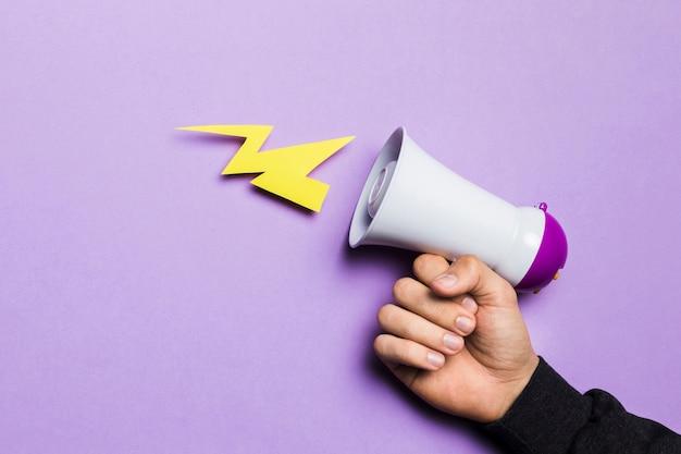 Hand der frau, die energiedonner mit megaphon zeigt Kostenlose Fotos