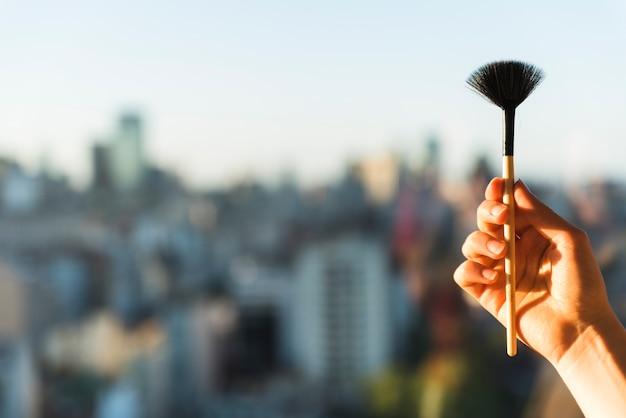 Hand der frau, die make-upbürste hält Kostenlose Fotos