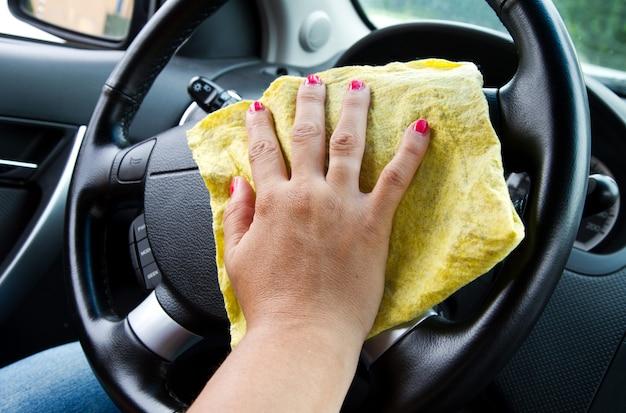 Hand der frau mit mikrofasertuchpolierscheibe eines autos Premium Fotos
