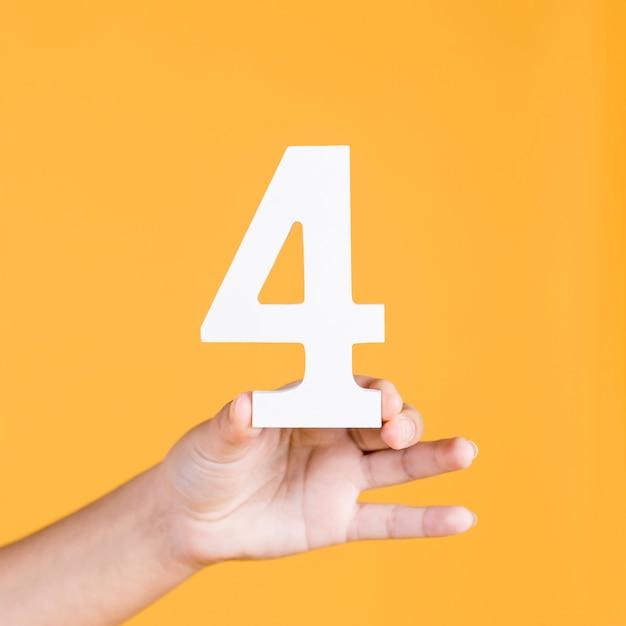 Hand der frau, welche die nr. 4 gegen einen gelben hintergrund hält Kostenlose Fotos